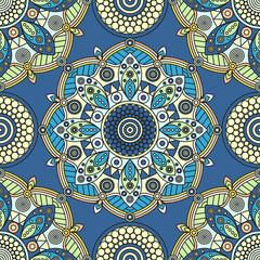 Seamless floral mandala pattern in blue, yellow, pale orange & turquoise green.