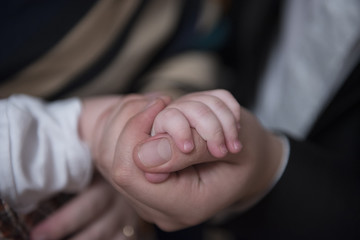 Father holding his little baby's hand in his hand, close-up