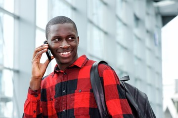 Smiling student with bag talking on phone