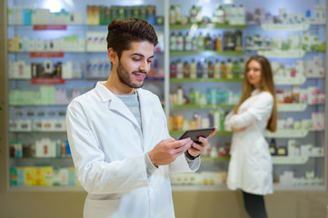 Portrait of pharmacist holding digital tablet in pharmacy,  in the background is a woman