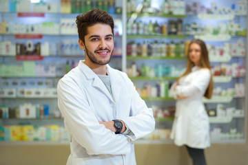 Portrait of pharmacist  in pharmacy, in the background is a woman