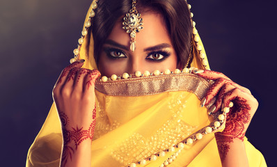 Beautiful indian girl . Young hindu woman model  with tatoo mehndi  and kundan jewelry . Traditional Indian costume yellow saree . Indian or Muslim woman covers her face. Fotomurales