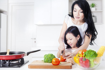 Beautiful mother and her girl cooking together