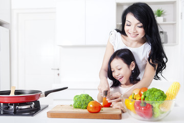 Beautiful mother teaches her girl to cook