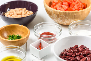 White And Red Kidney Beans, Chili Pepper, Parsley, Ketchup, Tomatoes, Olive Oil, Paprika And Yogurt Food Ingredients On White Wood Table