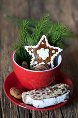 mug with Christmas gingerbread star shaped cookies, pieces of Stollen cake and Christmas tree twig over rustic wooden background