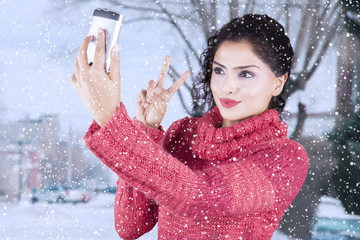 Indian woman taking selfie photo at winter time