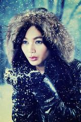 Sweet girl in fur jacket playing snow