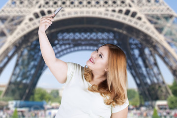 Woman taking selfie photo at eiffel tower