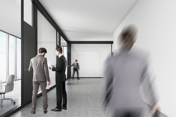 People walking in an office corridor with white and glass walls