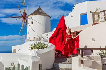 Beautiful woman in red dress on Santorini