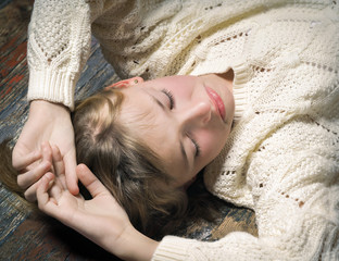 Beautiful young girl lying on the old wooden floor. The concept of relaxation, rest, reflection