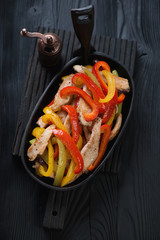 Chicken fajitas in a cast-iron pan over black wooden surface
