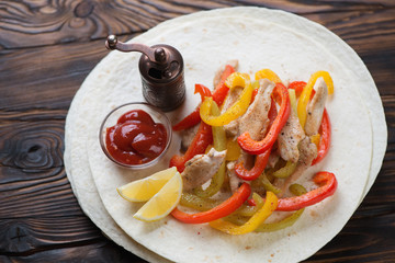 Tortilla bread filled with chicken fajitas over wooden surface