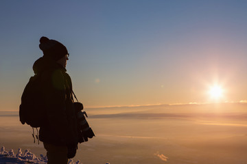 Male photographer on the mountain top. Sunset, winter. Snowy.
