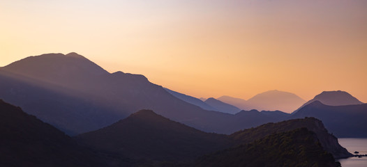 Silhouettes of layered mountains at sunset, nature landscape Wall mural