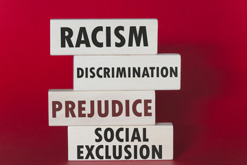 Racism, discrimination, prejudice and social exclusion message written on wooden tiles