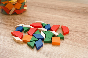 Multicolored pattern blocks on a dark wooden background