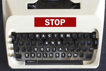 Retro typewriter with stop racism and social exclusion message written on it