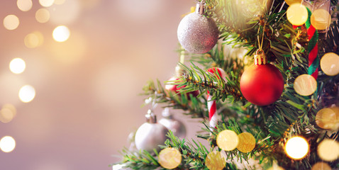 Closeup of red bauble hanging from a decorated Christmas tree with bokeh, copy space, Xmas holiday background.
