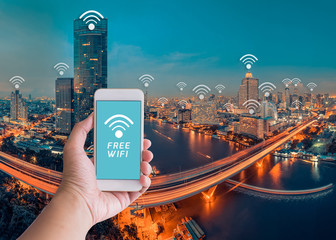 Handholding smartphone and cityscape with wifi icon,Technology a