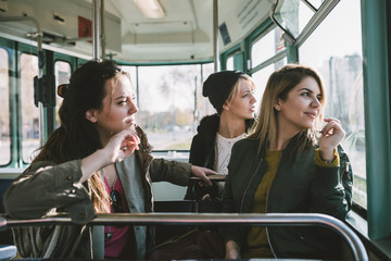 Three beautiful young women sitting in tram and looking through window.