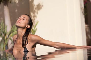 belle femme sexy qui bronze dans une piscine