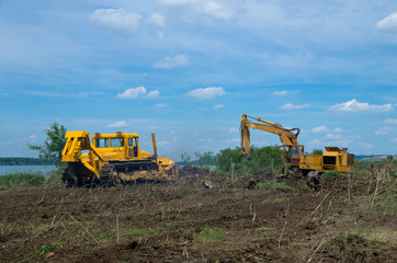 Excavator and bulldozer clearing forest land.