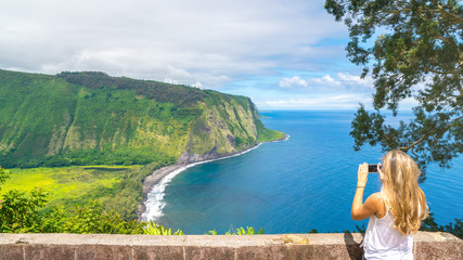 Young woman taking pictures of the amazing view in Waipio Valley, Big Island, Hawaii, Usa
