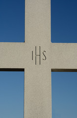 Granite cross with Christogram IHS engraved in center against blue sky