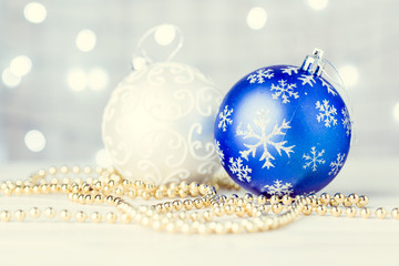White and blue Christmas balls on a holiday lights background