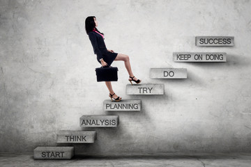 Businesswoman climbing ladder with strategy texts