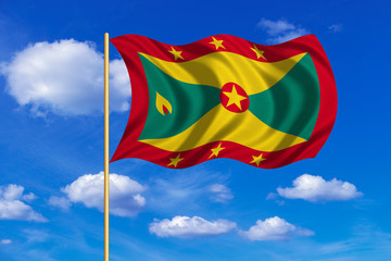 Flag of Grenada waving on blue sky background