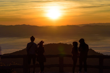 silhouette style of two couple on the top of view point in the mountain while watching sunrise and sea of fog or mist