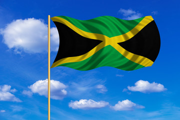 Flag of Jamaica waving on blue sky background