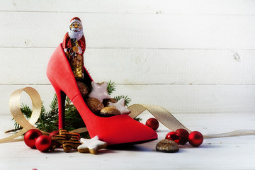 ladies red high heel shoe filled with sweets and christmas decoration for Nicholas day on the 6th December, white wooden background