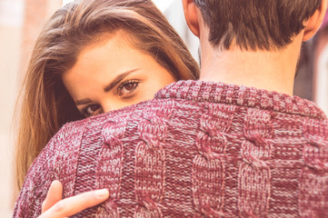 Attractive girl hugging her boyfriend and looking at the camera