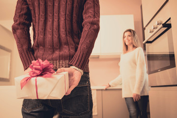 Man is hiding behind his back a gift for his girlfriend