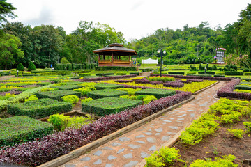 Country cottage garden path.  Thai style pavilion is located in the middle with tree background.