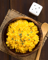 Pumpkin risotto prepared with pumpkin puree and sprinkled with fresh thyme leaves served in wooden bowl, photographed overhead with natural light (Selective Focus, Focus on the top of the risotto)