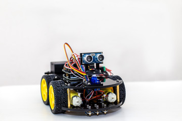 Robot on large wheels stands on a light background and looking t