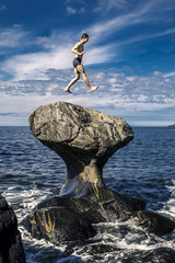 Young man is jumping on stone, Kannesteinen, Norway
