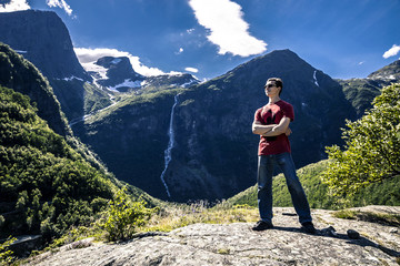 Young man is having fun hiking in Briksdalsbreen, Norway