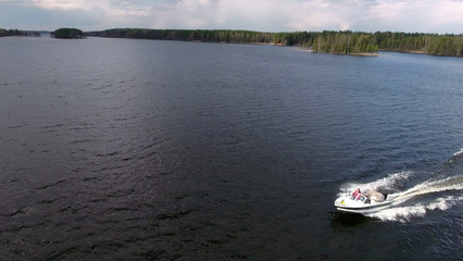 Side view of small powerboat riding in big lake, aerial view from drone, copyspace