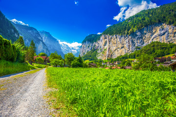 Fototapete - Famous Lauterbrunnen valley with gorgeous waterfall and Swiss Alps