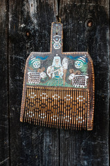 Old ukrainian traditional painted wooden wool comb hanging on dark timber background