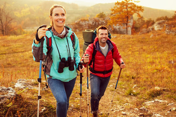 Couple hiking during autumn vacation with sticks and backpacks Wall mural