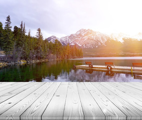 Wood table top on lake and mountain with sun ray effect backgrou