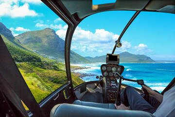 Poster Helicopter Helicopter cockpit flies in Misty Cliffs, Cape Peninsula in South Africa, with pilot arm and control board inside the cabin.