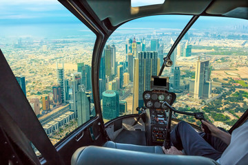 Poster Helicopter Helicopter cockpit flies in skyscrapers of Dubai downtown skyline on Sheikh Zayed Road, United Arab Emirates, with pilot arm and control board inside the cabin.